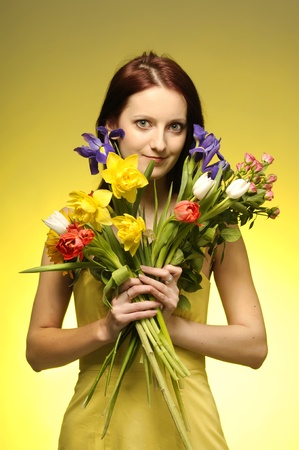 Portrait of cute  girl in yellov dress with a bunch of flowers photo