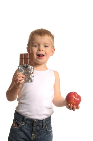 Picture of a little blond boy in white top and blue jeans eating chocolate and holding apple Stock Photo - 10895797