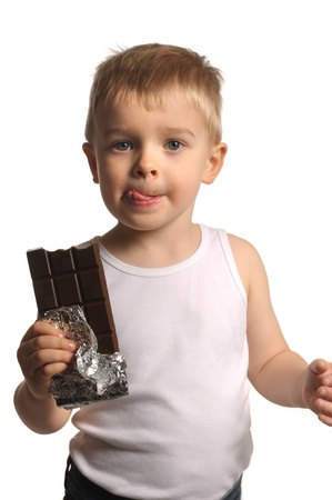 Picture of a little blond boy with his tongue out holding chocolate  Stock Photo