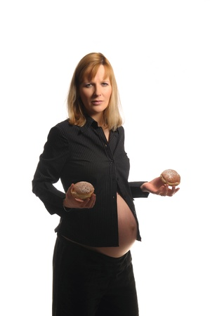 Picture of a young pregnant woman holding donuts in her hands Stock Photo - 10895758