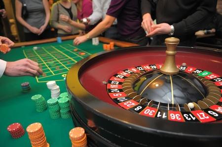 ruleta de casino: imagen de la ruleta y las pilas de fichas en una mesa verde Editorial