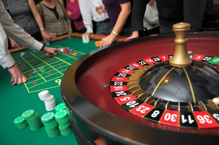 roulette table: picture of roulette and piles of chips on a green table