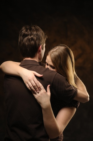 Couple in an embrace on an brown background
