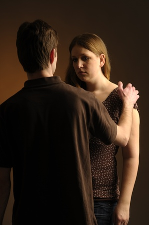Couple on dark background standing facing each Stock Photo - 10730935