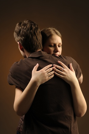 atone: Couple in an embrace on an dark background