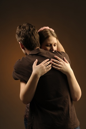 Couple in an embrace on an dark background photo