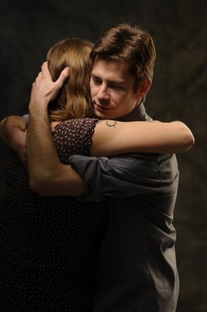 Paar in een omhelzing op een donkere achtergrond