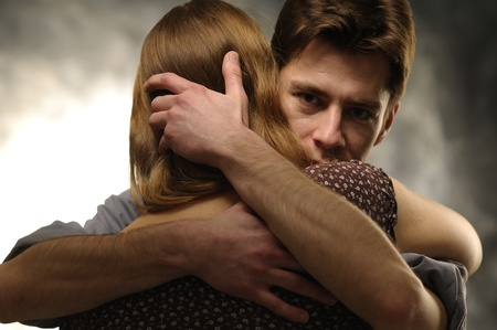 atone: Couple in an embrace on an gray background Stock Photo