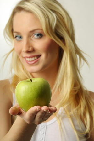 Sexy blond woman with green apple photo