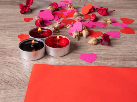 red envelope next to candles with red rose petals and ribbon on the table