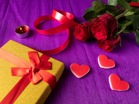 Yellow gift next to hearts and ribbon and red roses on purple background