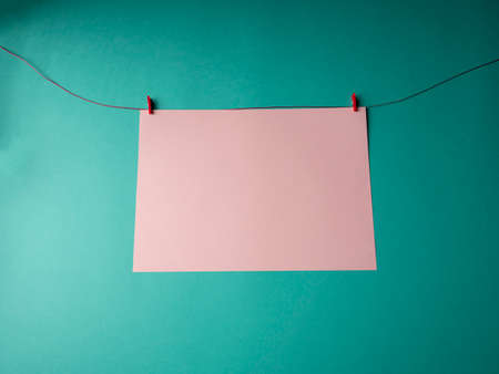 White paper that weighs on a red rope and is secured with two clothespins on a green background. A template for your project for valentine's day