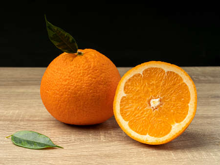 Orange slices on a wooden gray table on a dark background Fresh juice concept