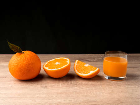 Glass glass with orange juice and orange stand on a wooden gray table on a dark background Fresh juice concept Reklamní fotografie