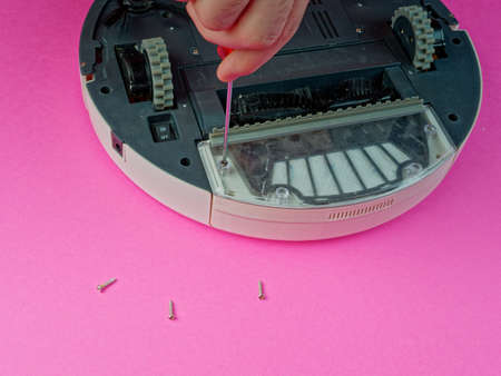 The robot vacuum cleaner is disassembled, the vacuum cleaner is being cleaned and disassembled, the concept of repairing a robot vacuum cleaner, and advertising prevention and replacement of filters Banque d'images