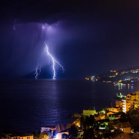jolt: Lightning into the sea over the night city. Yalta. Crimea. Ukraine. Russia Stock Photo