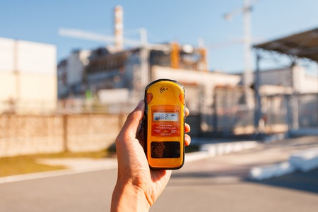 npp: Dosimeter and Nuclear Power Plant on the backgroundafter 30 years the explosion at the nuclear power plant. USSR soviet union built. Chernobyl Exclusion Zone. Ukraine Stock Photo