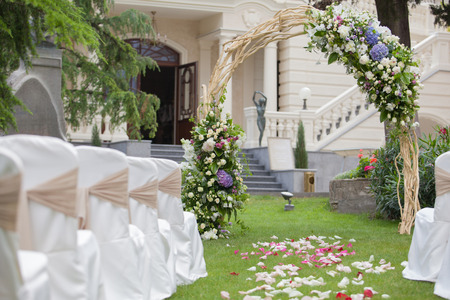 wedding table decor: Beautiful wedding gazebo with flower arrangements decorating