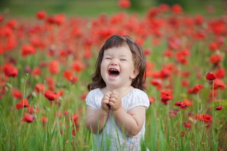 very happy child girl in poppy field photo