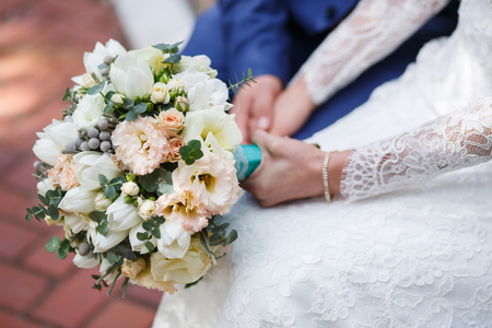 Bride and groom holding in hand beautiful wedding bouquet