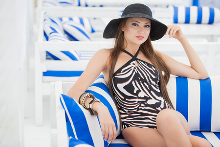 Beautiful young woman in bathing suit with black hat Stock Photo
