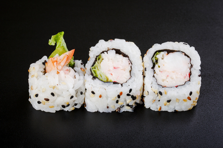 Japnes food. Sushi roll with shrimp and snow crab, on black backgorund Stock Photo