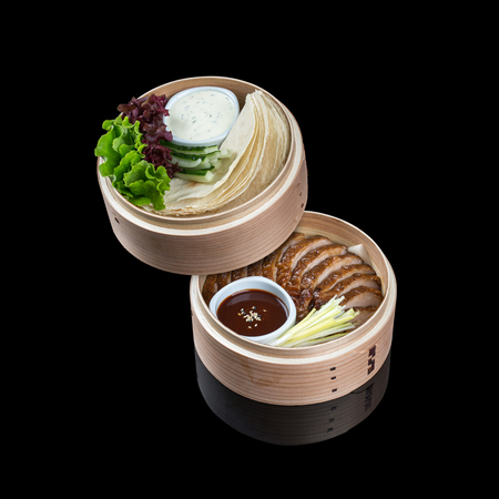 sins: Duck in Beijing in a bamboo dish, with a flat cake, sauce and cucumber. On a black background with reflection