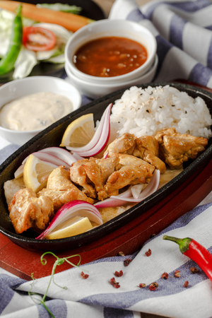 Skewers of grilled chicken in a pan with a side dish of rice Stock Photo
