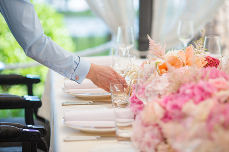 Waiters is serving dinner place on a wedding in a restaurant. Table decorated with flowers Stock Photo