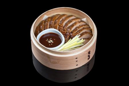 Pato en Beijing en un plato de bambú, con un pastel plano, salsa y pepino. Sobre un fondo negro con reflejo Foto de archivo - 77757712