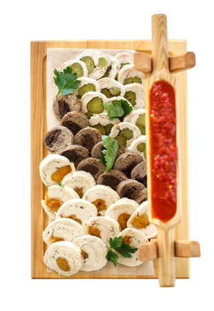 assorted meat rolls on a wooden platter isolated on white background