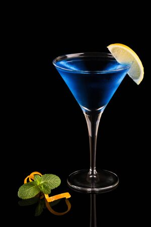 Glass of blue cocktail on a black background with reflection. Decorated with a slice of lemon. The color of the year 2020, classic blue.