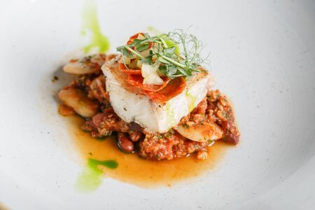 Codfish fillet on a bean pillow. Served in a plate with microgreens.
