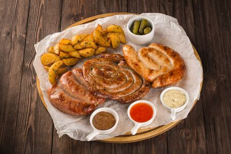 Assorted grilled sausages on a wooden board. Served with potato wedges, three kinds of sauce and pickled cucumbers.