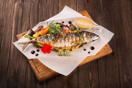 Grilled mackerel served on a wooden board with vegetables and sauce.