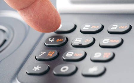 A finger dialing on a phone keypad