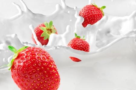 Strawberries splashing in to milk