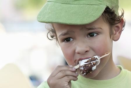 A boy eating an icecream outdoor