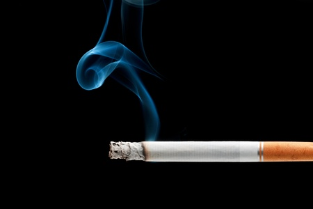 A cigarette burning isolated on a black background