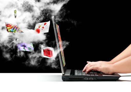 A female hands typing on a laptop with a cloud and some flying pictures