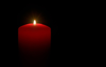 A red candle over a black background