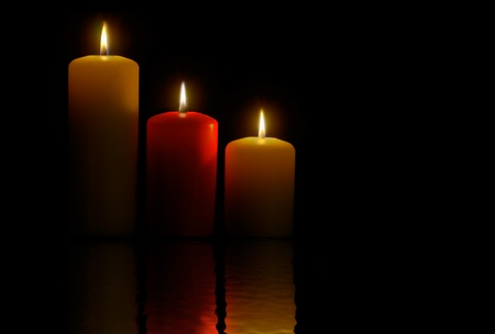 Three candles over a black background and its reflection