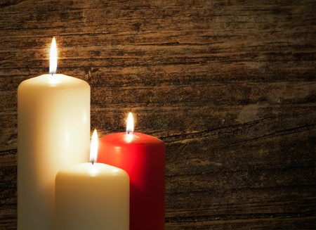 christmas memories: Three candles over a old wood background Stock Photo