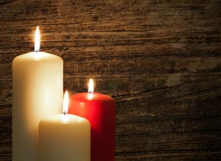 Tres velas sobre un fondo de madera vieja Foto de archivo