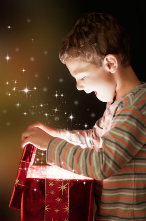 A surprised child opening and looking inside a magic gift Stock Photo - 11068124