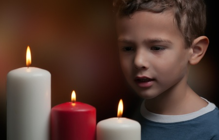 christmas memories: A child watching three candles burning