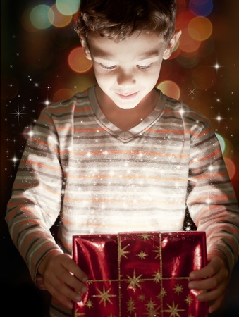 A surprised child opening and looking inside a magic gift photo