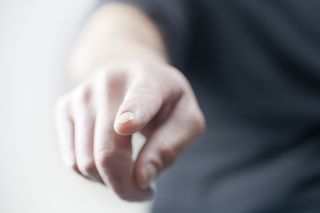 A finger pointing in the air. Shallow depth of field.
