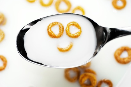 A spoon with milk and cereals showing a smile. Concept of a good breakfast to start a happy new day.