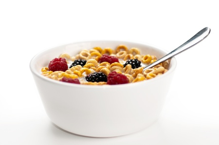 A bowl of cereals with fresh blackberries and raspberries with milk in a white background. Stock Photo
